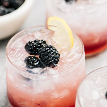 Three bramble cocktails on a cement background with a small bowl of blackberries in the background.