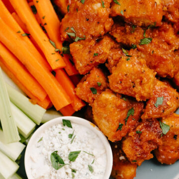 Buffalo chicken bites on a blue plate with carrot sticks, celery sticks, and bowl of blue cheese dressing.
