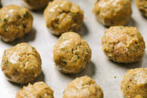 """Raw shawarma meatballs formed into 1.5"""" rounds on a baking sheet."""