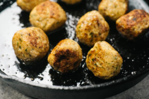Chicken shawarma meatballs browning in a cast iron skillet.