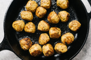 Cooked chicken shawarma meatballs in a cast iron skillet.