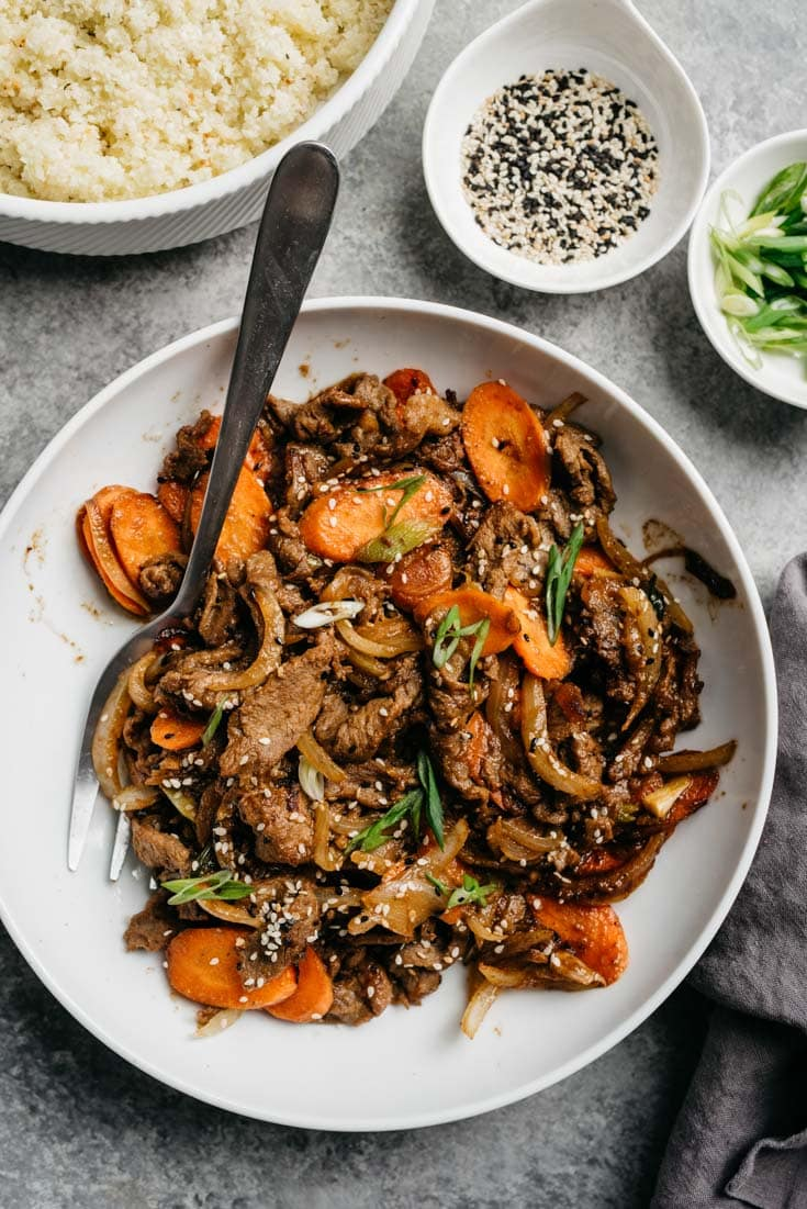 Whole30 korean beef bbq in a bowl with carrots, surrounded by smaller bowls of cauliflower rice, sesame seeds, and green onions.