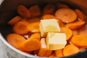 Sliced carrots in a pot with water, cornstarch, butter, honey, and salt.