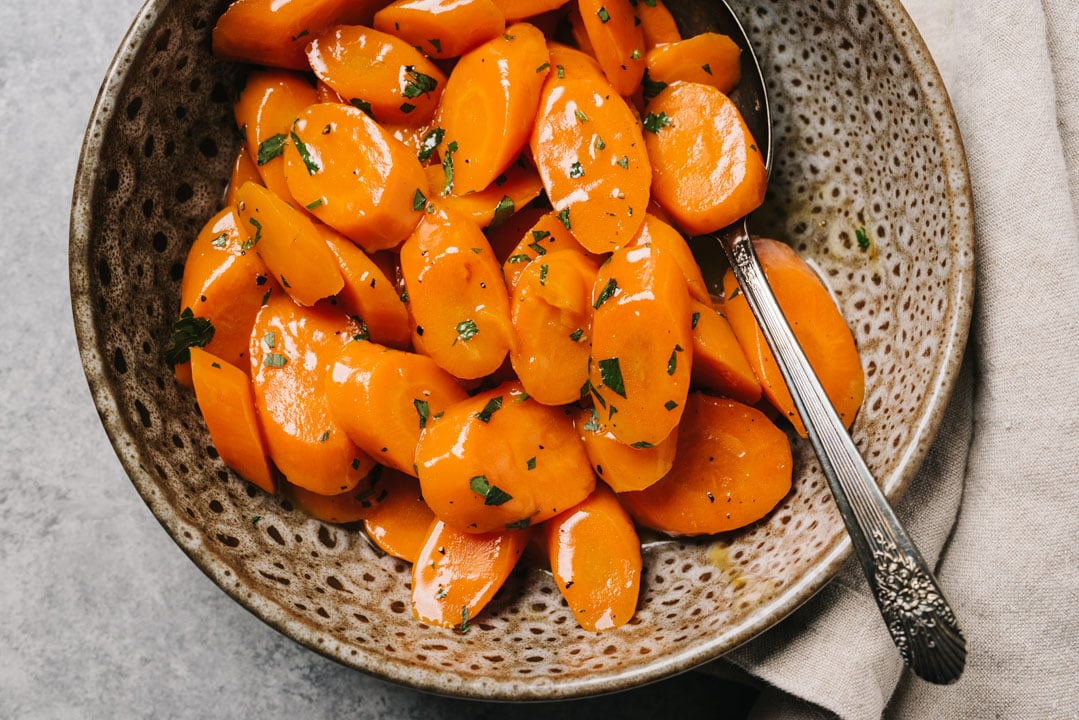 Glazed carrots garnished with parsley in a brown speckled bowl with a vintage serving spoon and tan linen napkin on a concrete background.
