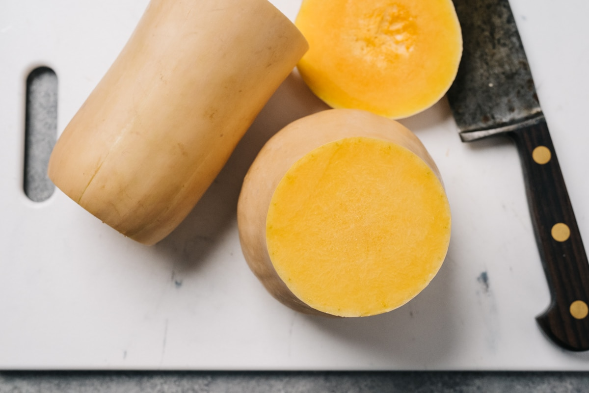 A butternut squash with ends trimmed, sliced in half, on a cutting board with a chef's knife.