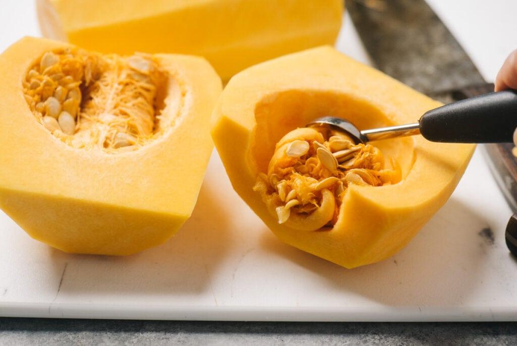 Scooping seeds from a butternut squash using a melon baller.