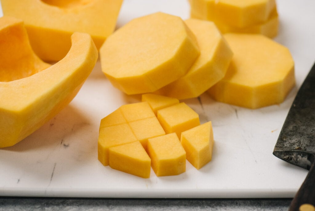 Thick slices of butternut squash on a cutting board and diced pieces next to it.