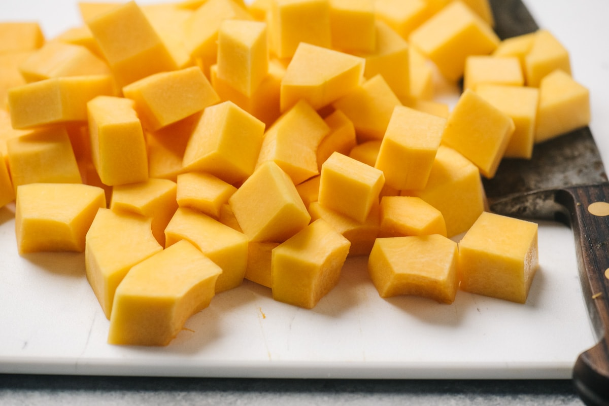 Diced butternut squash on a cutting board with a chefs knife.