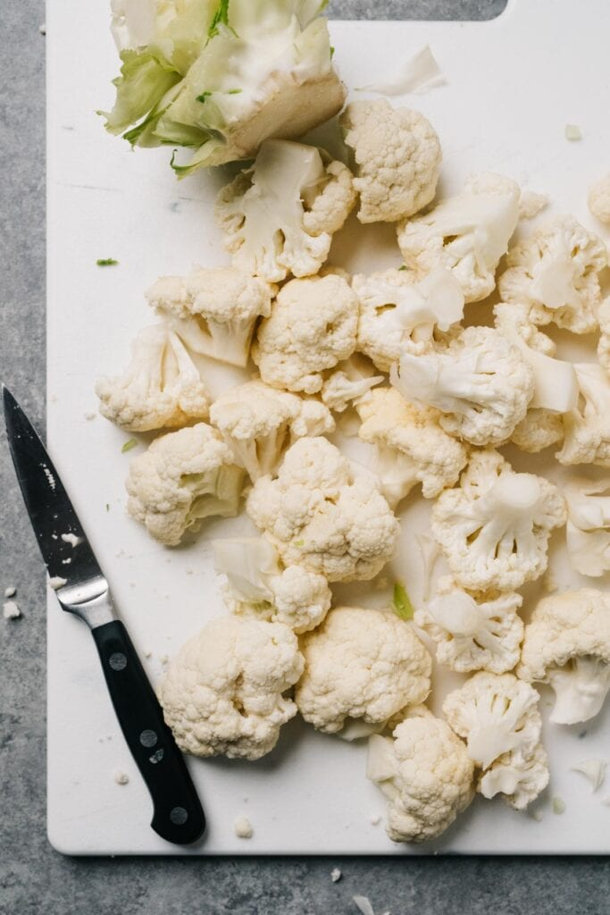 Cauliflower florets on a cutting board with a paring knife and trimmed down cauliflower stalk.