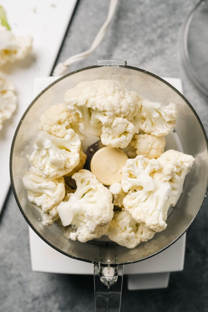 Cauliflower florets in the bowl of a food processor.