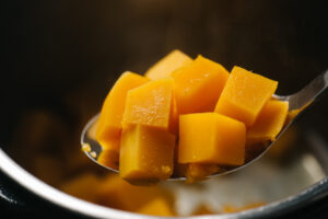 Instant pot butternut squash cubes on a slotted spoon.