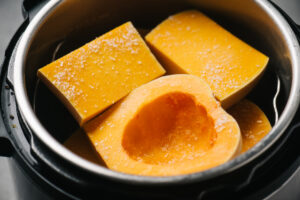 Chunks of unpeeled butternut squash in an instant pot sprinkled with salt.