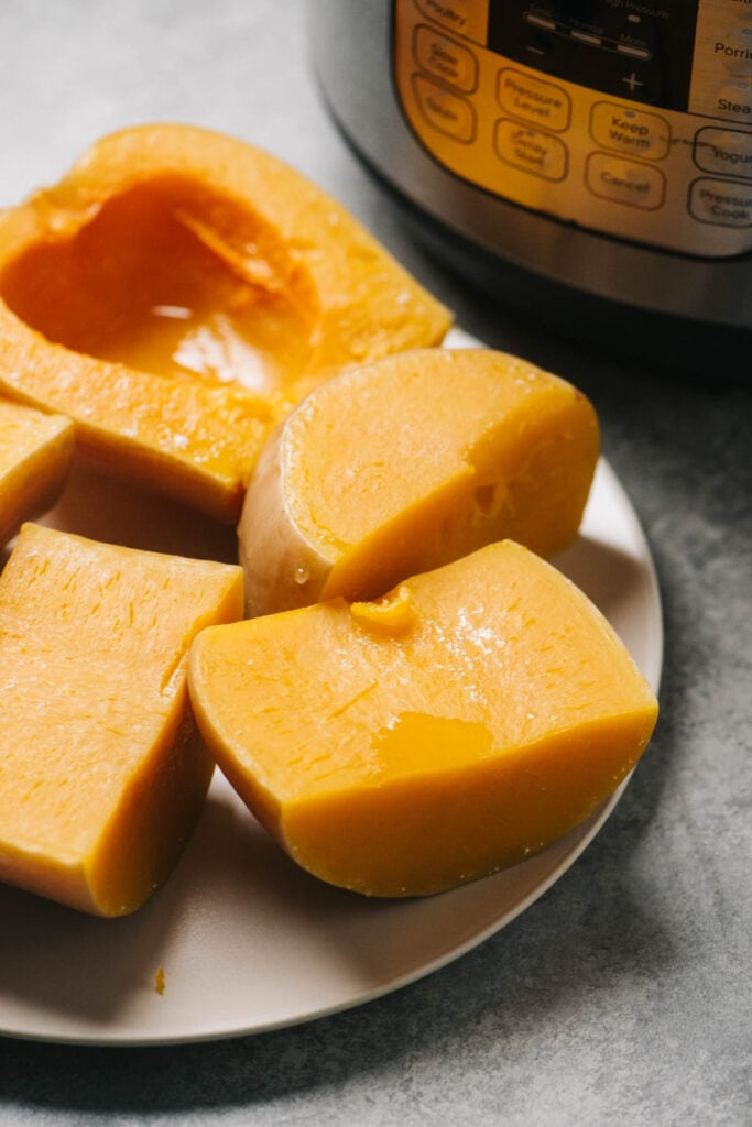 Steamed butternut squash halves on a plate in front of an instant pot.