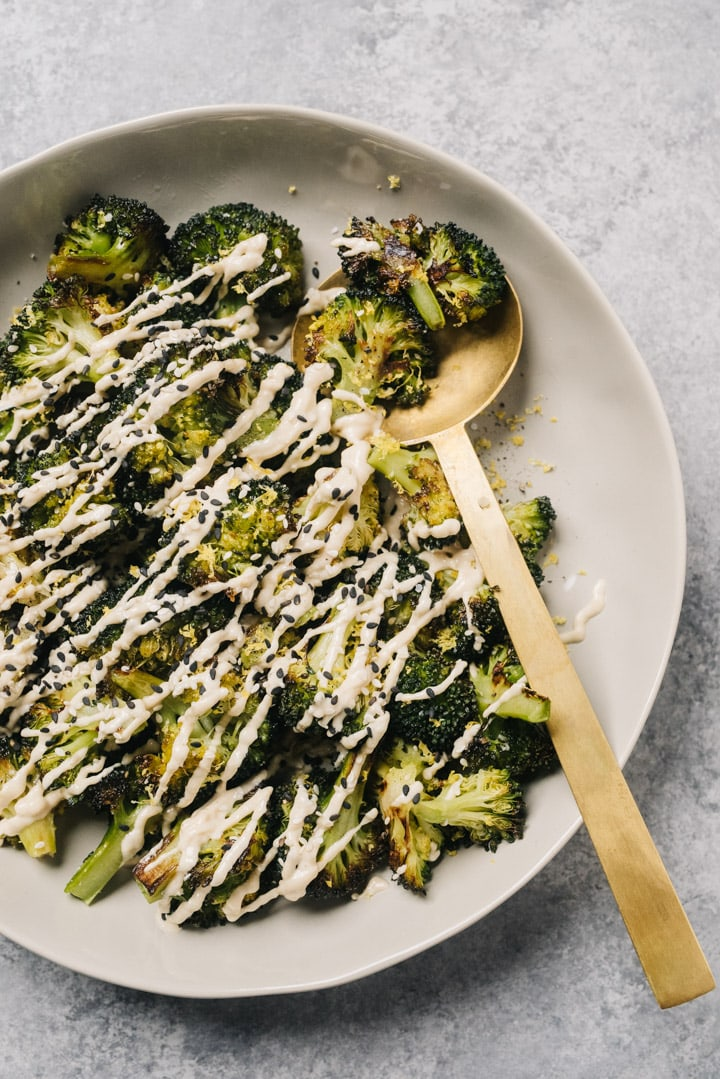 Keto roasted broccoli drizzled with tahini sauce in a tan serving bowl with a gold serving spoon.