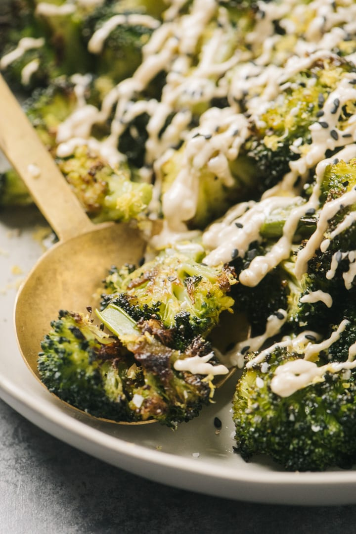 Side view, a gold serving bowl tucked into keto roasted broccoli drizzled with tahini sauce.