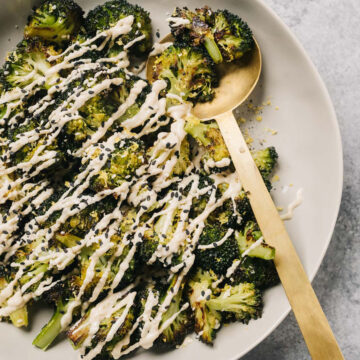 Keto roasted broccoli in a tan serving bowl drizzled with tahini sauce.