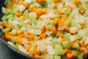 Sautéed onions, carrots, and celery in a skillet.