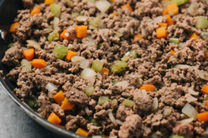 Sauteed onions, carrots, and celery with ground beef in a skillet.