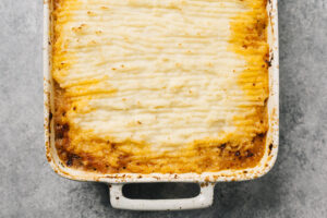 Keto shepherds pie fresh from the oven in a casserole dish on a concrete background.
