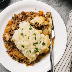 A serving of keto shepherd's pie on a white plate with a silver fork on a concrete surface with a striped linen napkin.