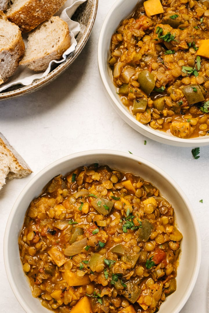 Two bowls of cajun lentil stew on a concrete background with a bowl of bread slices to the side.