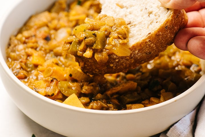 Dipping a slice of sourdough bread into a bowl of lentil stew.