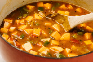 Lentil stew with cajun seasoning and sweet potato in a red dutch oven before simmering.