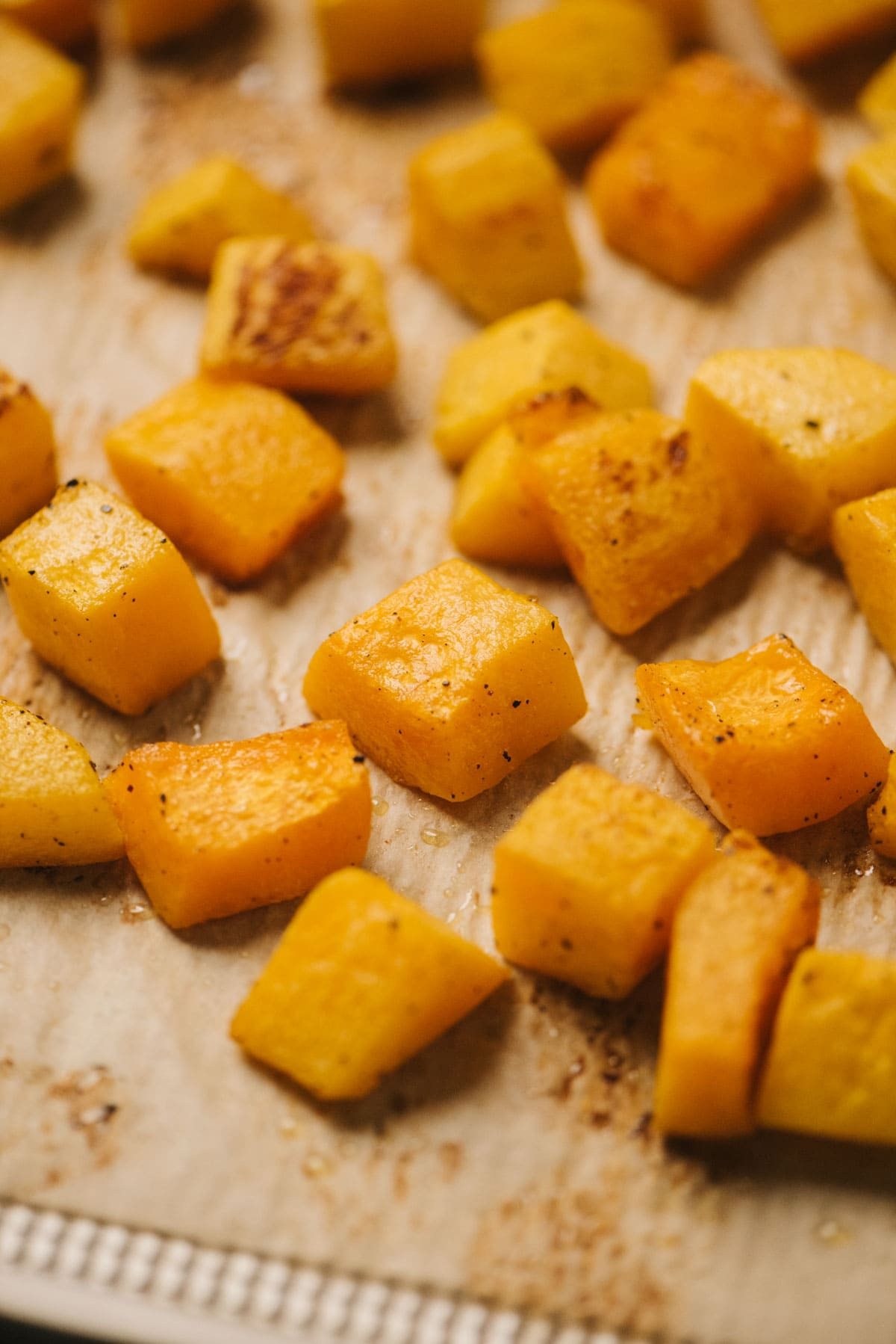 Roasted butternut squash cubes on a parchment lined baking sheet.