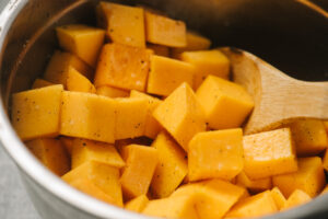 Diced butternut squash tossed with olive oil, salt, and pepper in a metal mixing bowl.