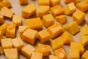 Diced butternut squash tossed with olive oil, salt, and pepper arranged on a parchment lined baking sheet.