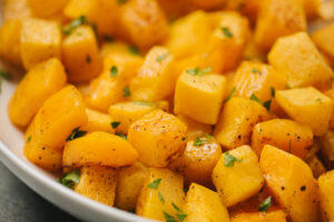 Roasted butternut squash in a serving bowl garnished with fresh chopped parsley.