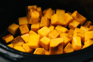 Cubed pieces of butternut squash in a slow cooker sprinkled with salt, cinnamon, and nutmeg.