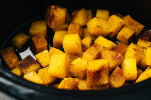 Cooked butternut squash cubes in a crockpot.