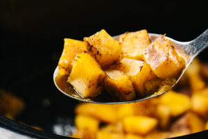 Slow cooker butternut squash cubes on a slotted spoon.