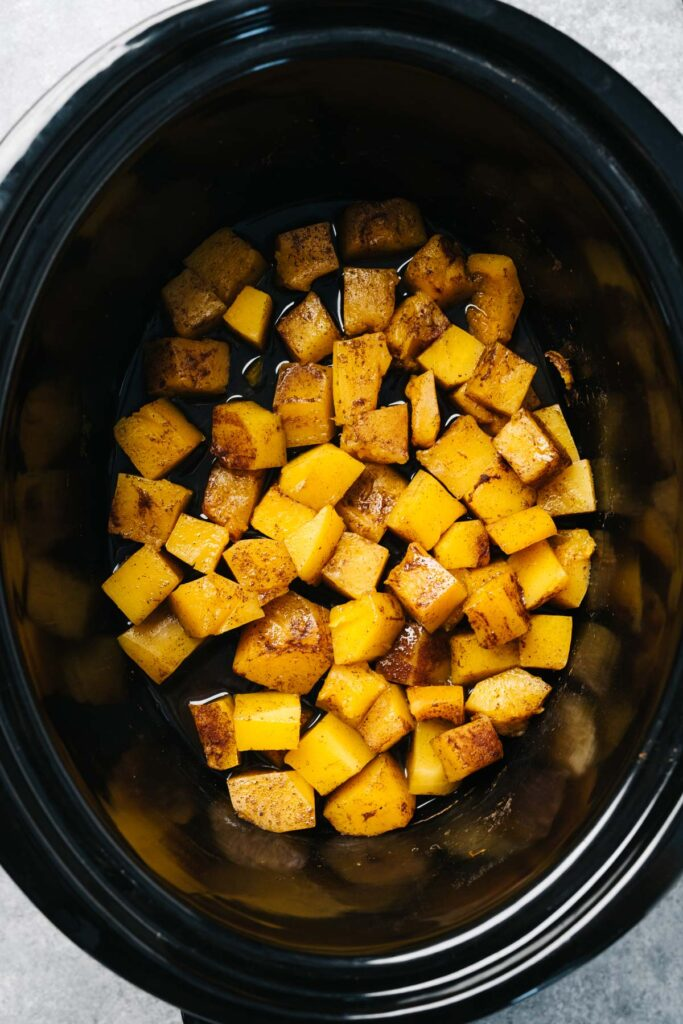 Butternut squash cubes in a slow cooker seasoned with salt, cinnamon, and nutmeg.