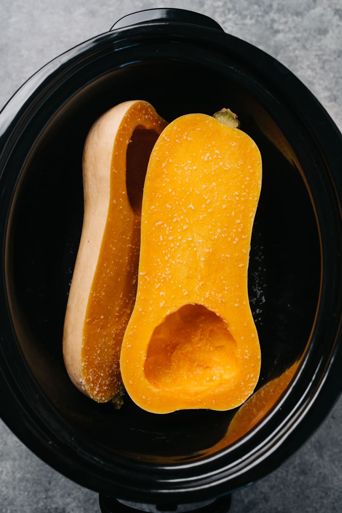 A butternut squash sliced in half with seeds removed in a slow cooker.