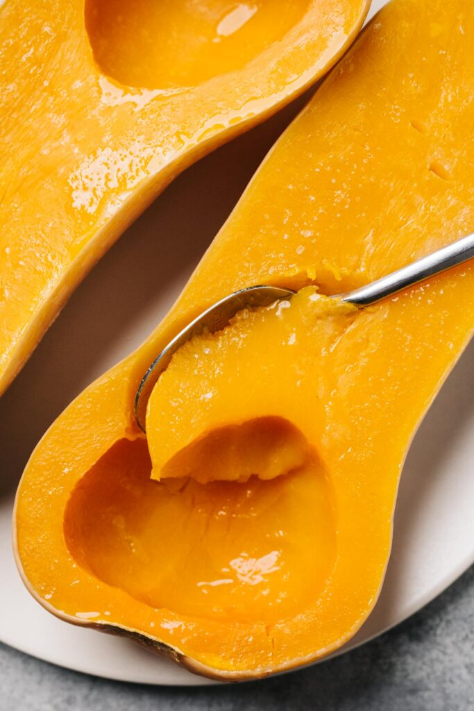 A spoon removing a piece of flesh from a butternut squash half cooked in a slow cooker.