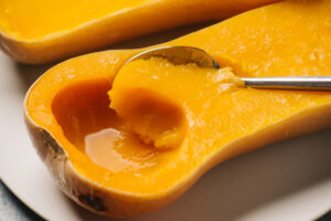 A spoon scooping the flesh from butternut squash cooked in a slow cooker.