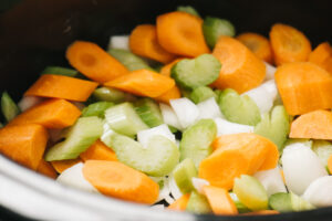 Chopped onions, carrots, and celery layered in a slow cooker.