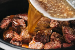 Pouring beef broth into a slow cooker with browned chuck roast and diced vegetables.