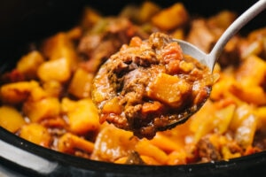 A ladle of whole30 slow cooker beef stew.