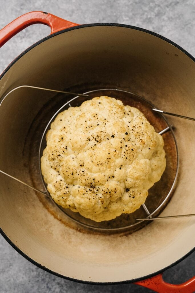 A head of whole roasted cauliflower on a trivet in a dutch oven.