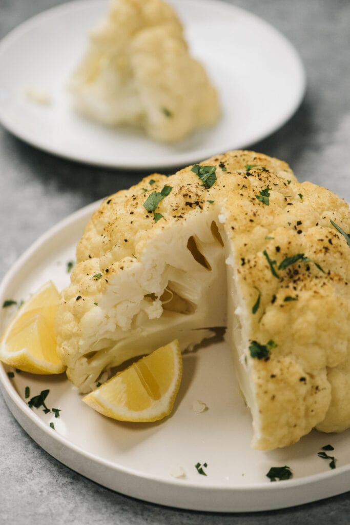 Whole roasted cauliflower on a white plate with a wedge missing, drizzled with olive oil, lemon juice, and parsley.