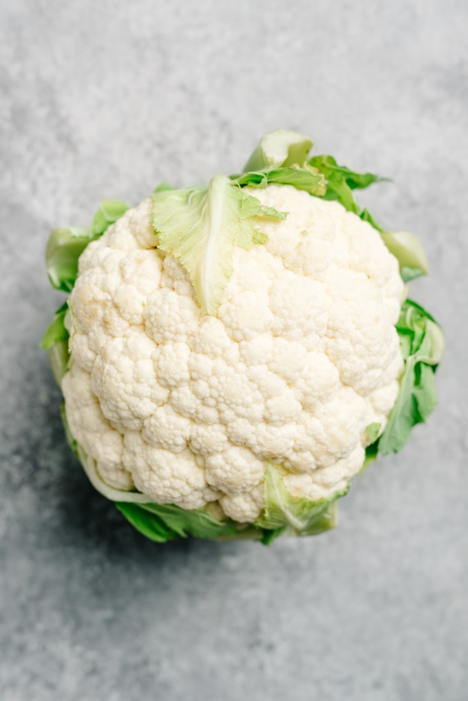 A whole head of cauliflower on a cement background.
