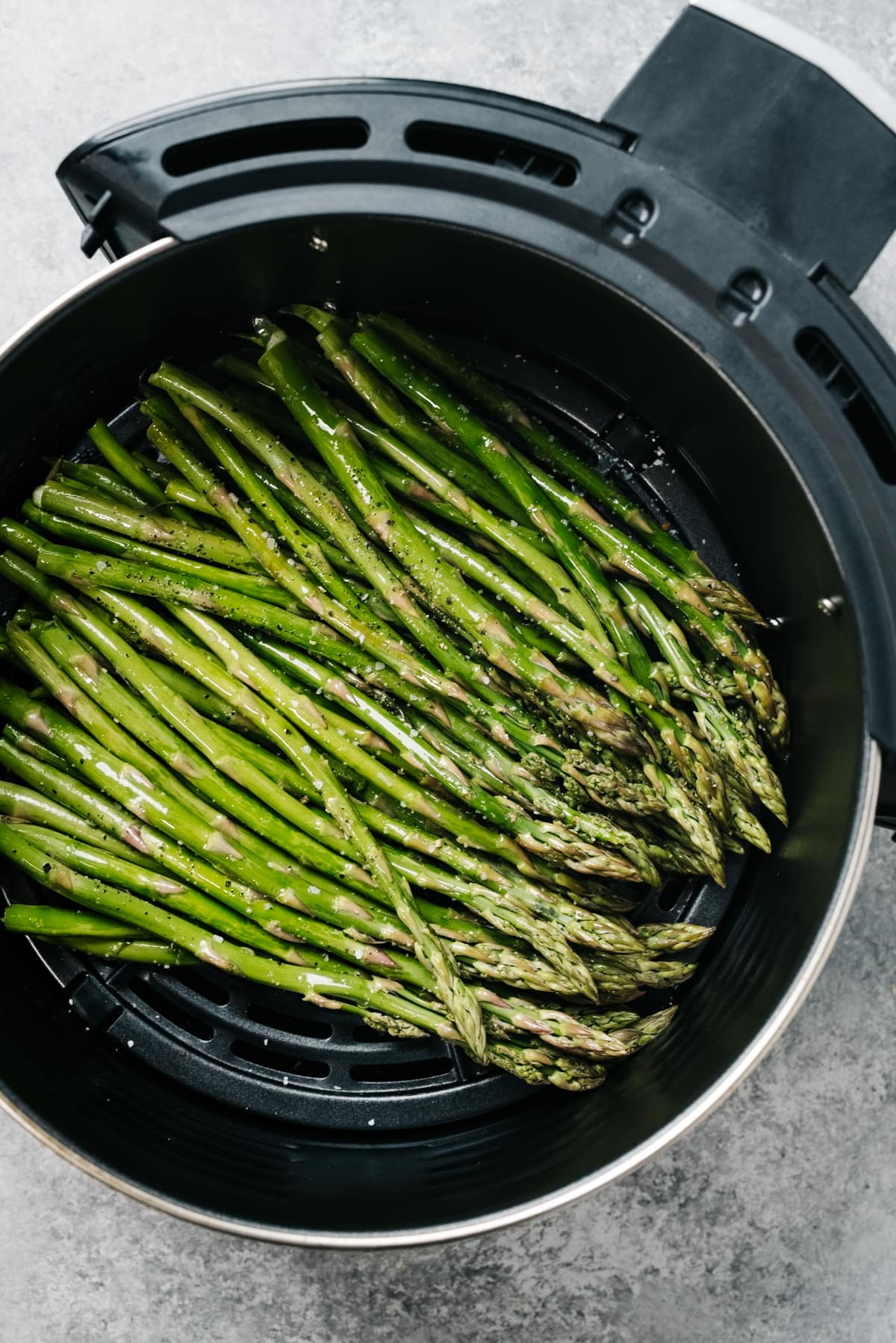 From overheard, asparagus spears tossed with olive oil, salt, and pepper in the basket of an air fryer.