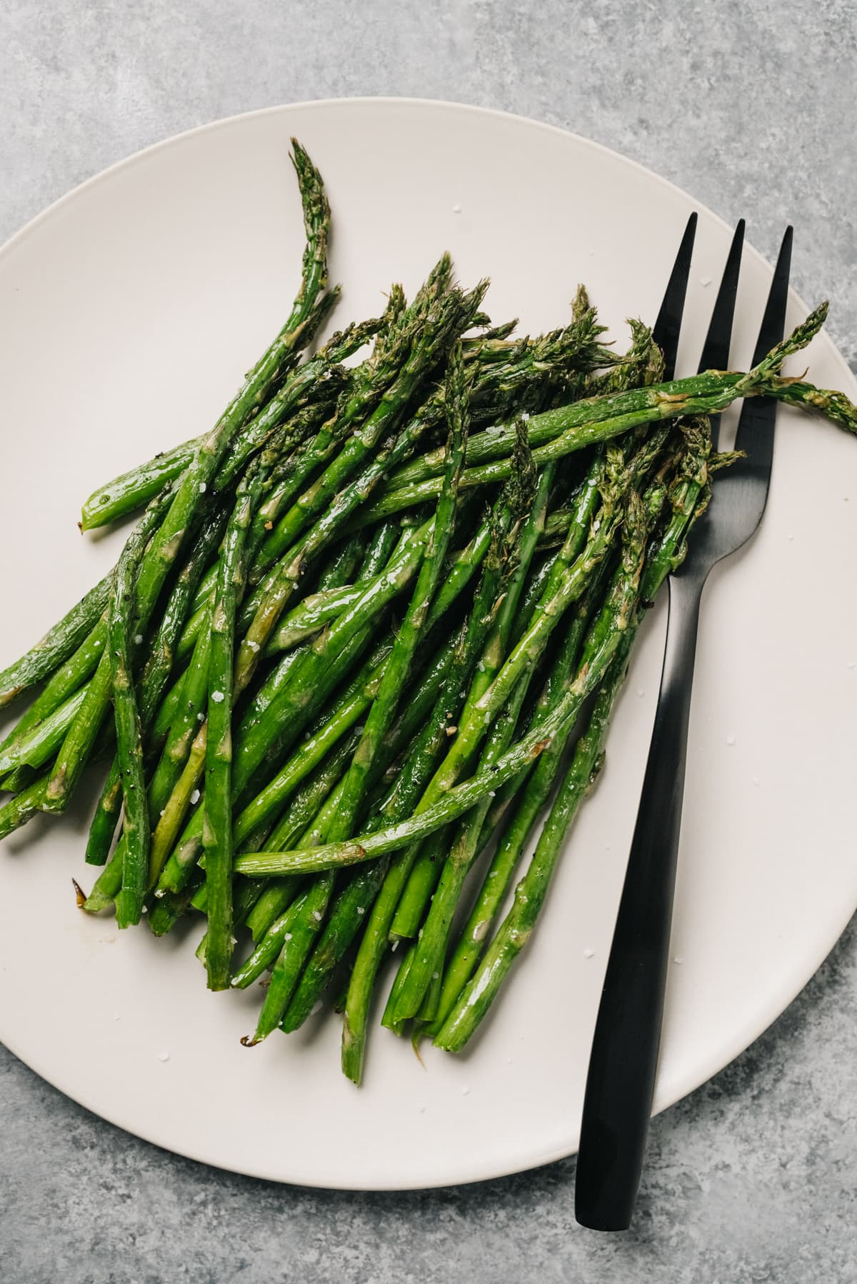 Air fryer asparagus on a cream plate with a silver serving fork on a concrete background.
