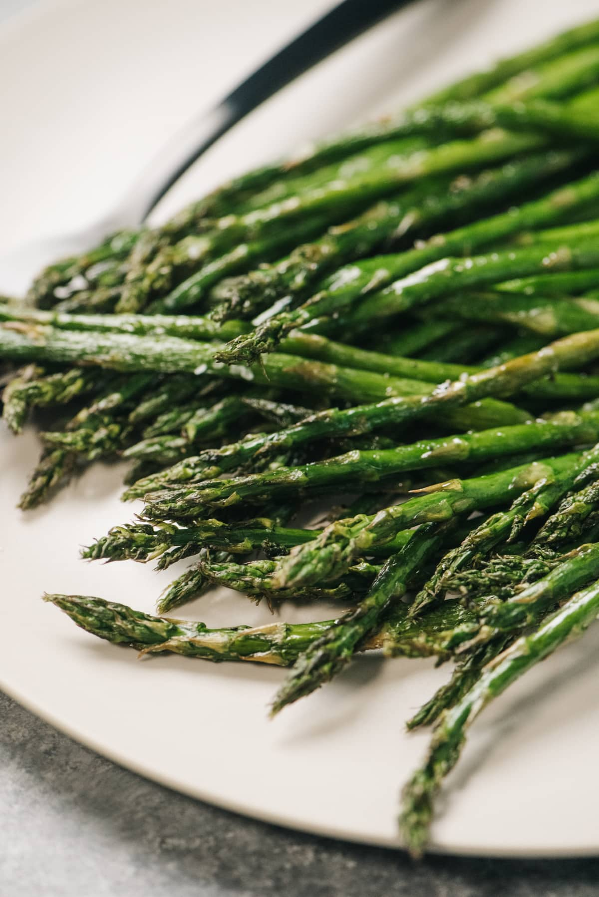Side view, air fryer asparagus spears on a cream platter with a silver serving fork.