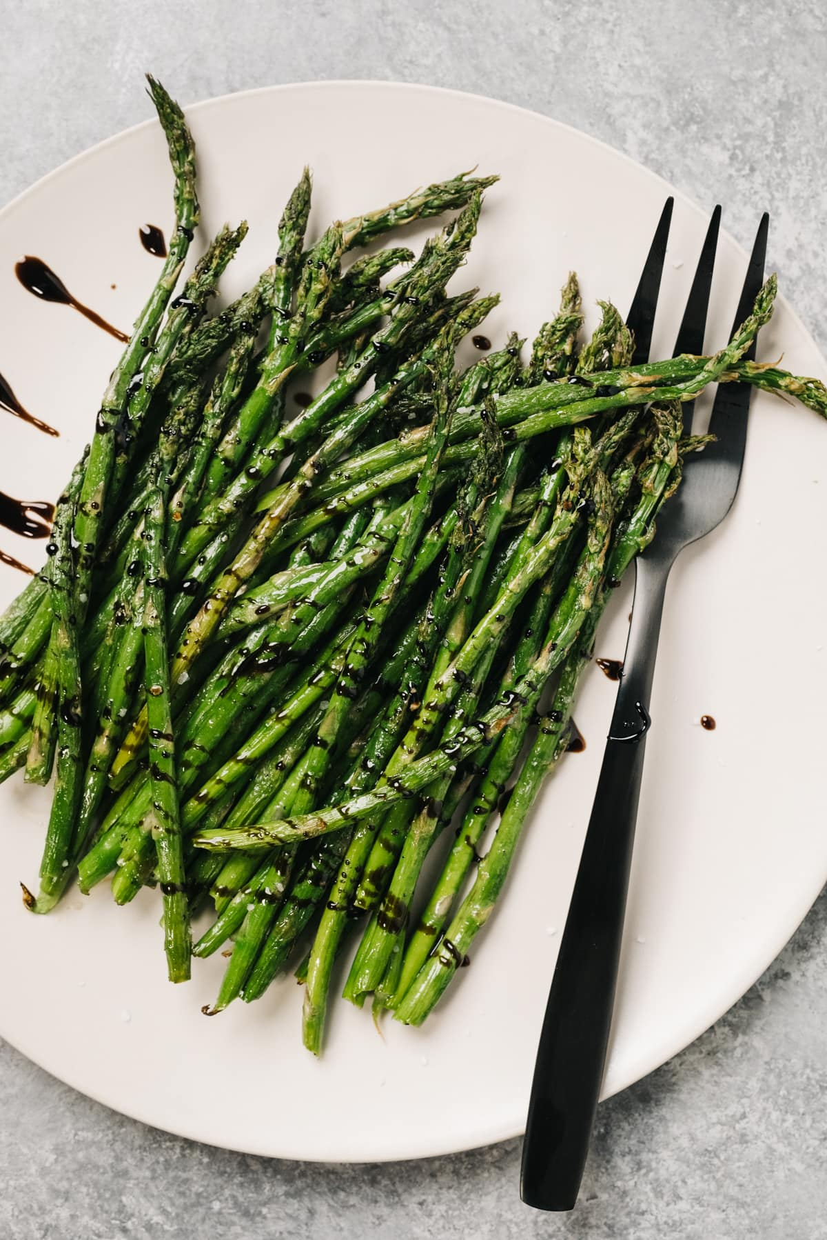 Asparagus cooked in an air fryer on a cream serving plate with a serving fork, drizzled with balsamic reduction.