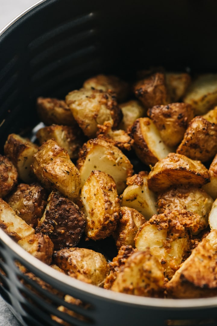 Side view, garlic parmesan potatoes in the basket of an air fryer.
