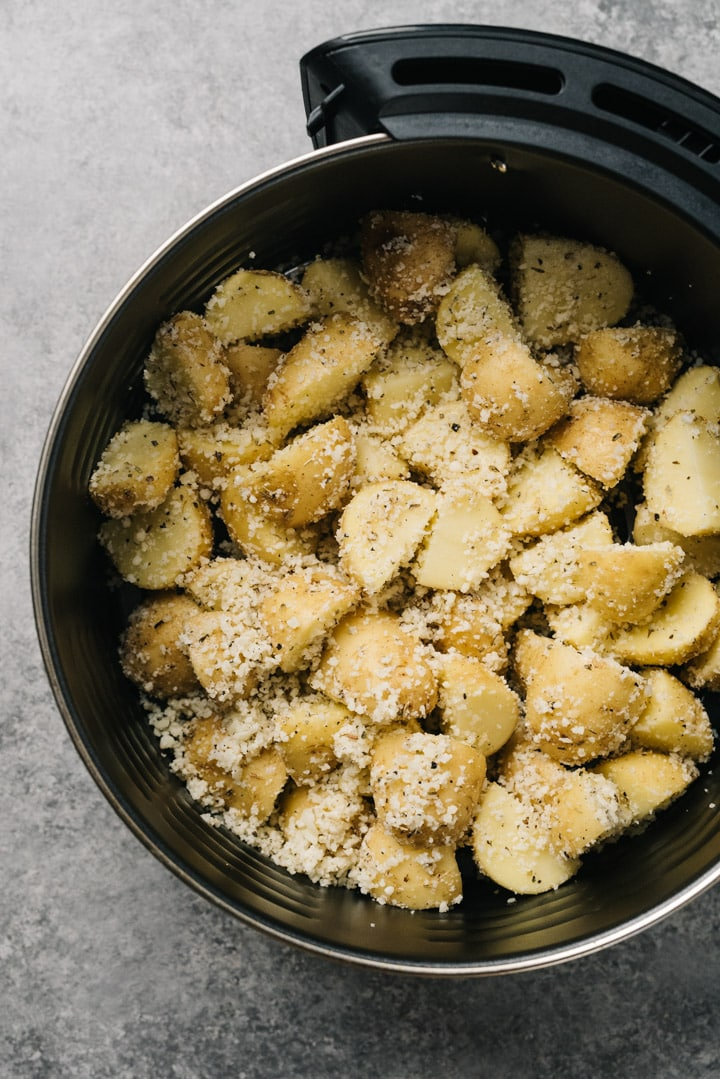 From overhead, garlic parmesan seasoned potatoes in the basket of an air fryer before cooking.